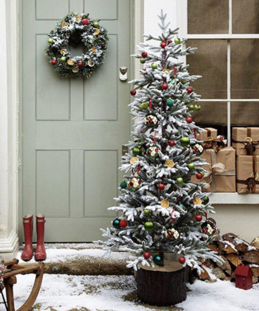 рождественский венок на двери и украшенная елка